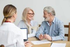 愉快的资深夫妇谈论房子购买在会议上与ag 免版税库存图片