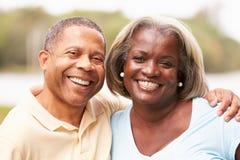愉快的资深夫妇画象在庭院里 免版税图库摄影