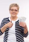 愉快的资深女性举行的货币美元和显示赞许,金融证券的概念在晚年的 库存图片