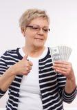 愉快的资深女性举行的货币美元和显示赞许,金融证券的概念在晚年的 免版税图库摄影