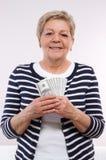 愉快的资深女性举行的货币美元,金融证券的概念在晚年的 库存照片