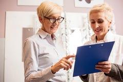 愉快的资深女性患者与成熟验光师协商 免版税图库摄影