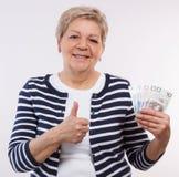 愉快的资深女性藏品擦亮剂货币金钱和陈列赞许,在晚年的金融证券 免版税图库摄影