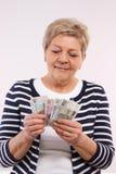 愉快的资深女性计数的波兰货币金钱,金融证券的概念在晚年的 免版税库存图片