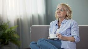 愉快的资深妇女坐沙发和饮用的茶、健康和退休 影视素材
