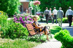愉快的资深妇女步行在美丽的夏天庭院和呼吸新鲜空气 免版税库存图片