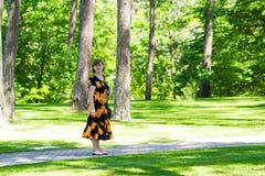 愉快的资深妇女步行在美丽的夏天庭院和呼吸新鲜空气 免版税库存照片