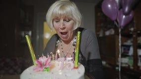 愉快的资深妇女藏品蛋糕 庆祝 吹的生日蜡烛 股票录像