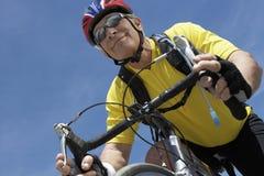 愉快的资深男性骑自行车者骑马自行车 库存照片