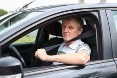 愉快的资深男性紧固坐在汽车的安全带 免版税图库摄影