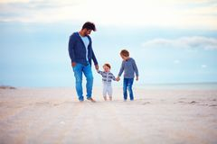 愉快的走含沙秋天的父亲和儿子在海附近靠岸 免版税图库摄影