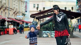 愉快的走和笑在城市的母亲和她的小儿子