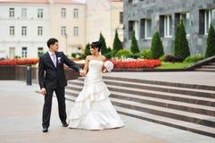 愉快的走在一个老镇的新娘和新郎 免版税库存照片