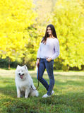 愉快的走在公园的妇女所有者和狗 免版税库存图片