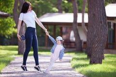 愉快的走在公园的母亲和女儿 免版税图库摄影