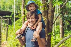 愉快的走在夏天的父亲和小男孩停放 收养和人概念 免版税库存图片