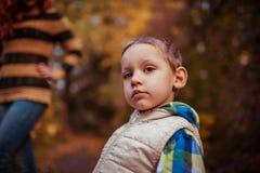 愉快的走在秋天森林里的母亲和她的小儿子 库存照片