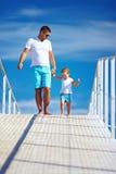 愉快的走在蓝天天际的父亲和儿子 免版税库存图片