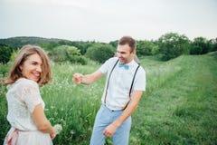 愉快的走在绿草的新娘和新郎 免版税图库摄影