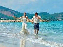 愉快的跑在一个美丽的热带海滩的新娘和新郎 库存图片