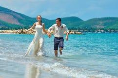 愉快的跑在一个美丽的热带海滩的新娘和新郎 库存照片