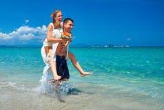 愉快的跑在一个美丽的热带海滩的新娘和新郎 免版税库存图片