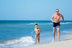 愉快的跑在海滩的父亲和他小的太阳 免版税库存照片