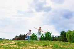 愉快的跑在草微笑的母亲和儿子 免版税图库摄影