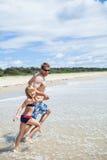 愉快的跑沿海滩的父亲和女儿 免版税库存照片