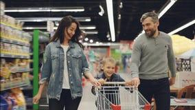 愉快的跑通过有购物车的超级市场的家庭父亲、母亲和孩子的慢动作,微笑和 股票视频