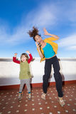 愉快的跳跃在大阳台的母亲和小孩 库存图片