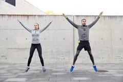 愉快的跳跃男人和的妇女户外 库存照片
