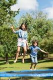 愉快的跳跃高在绷床的男孩和女孩在公园 库存照片