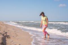 愉快的运动的妇女,有飞行头发的,沿海浪走 库存照片