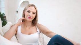 愉快的迷人的欧洲妇女中景画象坐长沙发在舒适白色内部 股票录像