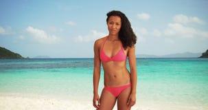 愉快的适合亚洲千福年穿站立在海滩微笑的比基尼泳装 免版税库存照片