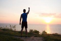 愉快的适合赛跑者观看的日出或日落与rised拳头,年轻运动员草的在日出期间在海 免版税图库摄影