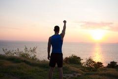 愉快的适合赛跑者观看的日出或日落与rised拳头,年轻运动员草的在日出期间在海 免版税库存图片