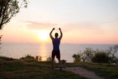 愉快的适合赛跑者观看的日出或日落与rised拳头,年轻运动员草的在日出期间在海 库存图片