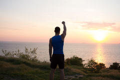 愉快的适合赛跑者观看的日出或日落与rised拳头,年轻运动员草的在日出期间在海 库存照片