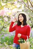 愉快的逗人喜爱的亚洲中国自然美好的妇女举行花穿戴一个帽子在春天公园享受业余时间 库存图片