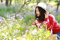 愉快的逗人喜爱的亚洲中国自然美好的妇女举行花穿戴一个帽子在春天公园享受业余时间 库存照片