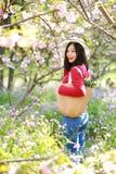 愉快的逗人喜爱的亚洲中国自然美好的妇女举行花穿戴一个帽子在春天公园享受业余时间 免版税库存图片