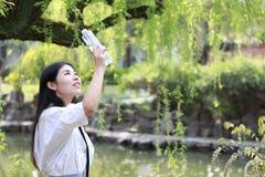 愉快的逗人喜爱的可爱的美丽的女孩高中大学生由一个湖在夏天公园饮料水中享受业余时间 库存照片