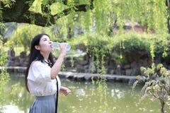 愉快的逗人喜爱的可爱的美丽的女孩高中大学生由一个湖在夏天公园饮料水中享受业余时间 免版税库存图片