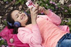 愉快的逗人喜爱的女孩微笑的耳机 库存图片