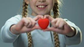 愉快的逗人喜爱的女孩陈列玩具心脏到照相机里,感觉爱并且需要 股票视频