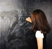 愉快的逗人喜爱的学生画象在黑板后面的t教室 库存照片