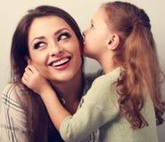 愉快的逗人喜爱的孩子女孩耳语秘密对她微笑的母亲 库存照片