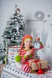 愉快的逗人喜爱的小女孩在家坐在装饰的新年室的镶边睡衣穿戴了 免版税库存照片
